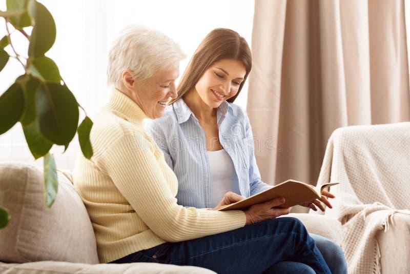 Rodzinny szczęście i wspominki Mamy i córki przyglądający album zdjęcia royalty free