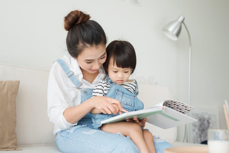 rodzinny szczęśliwy target2231_0_ Ładna młoda azjata matka czyta książkę fotografia stock