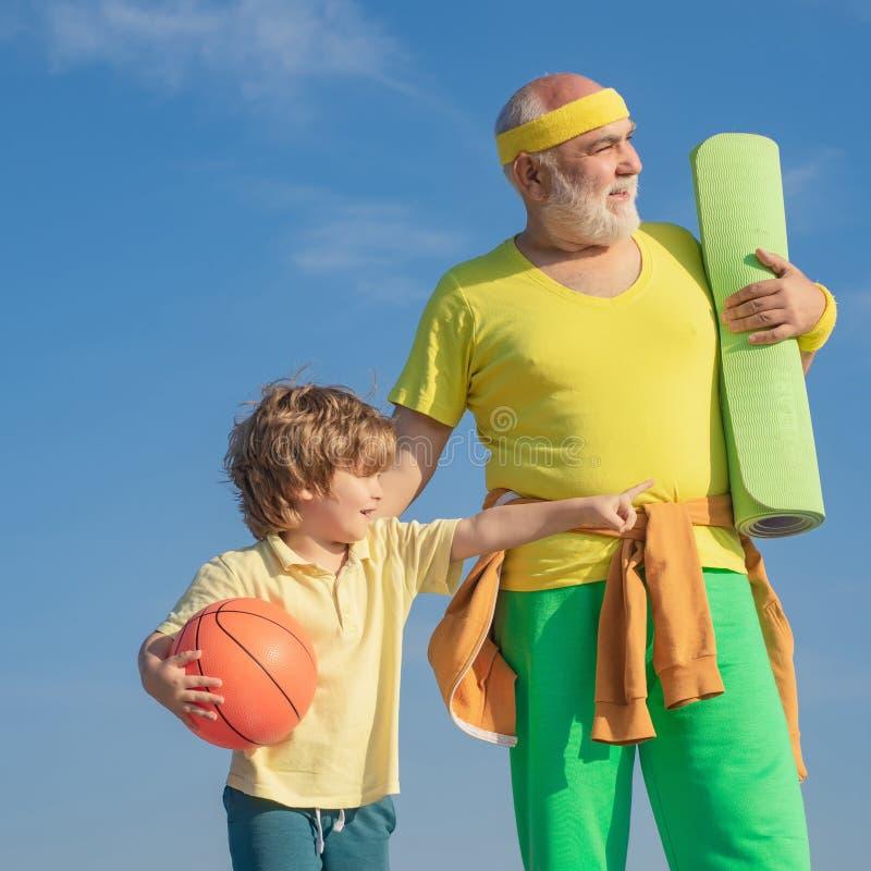 rodzinny szcz??liwy target2231_0_ Sportowa dziad i zdrowy dzieciak z koszykówki piłką na niebieskiego nieba tle Sport dla trochę fotografia stock