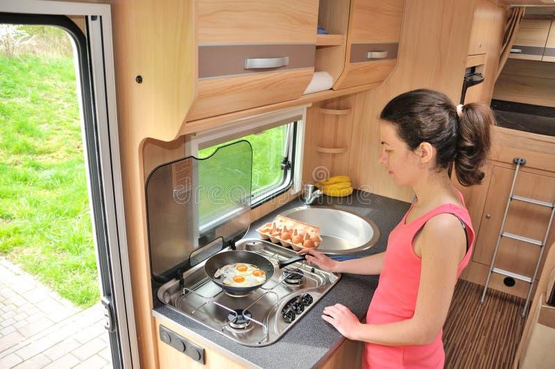 Rodzinny wakacje, RV wakacyjna wycieczka, podróż i camping, kobiety kucharstwo w obozowiczu, motorhome wnętrze zdjęcie stock