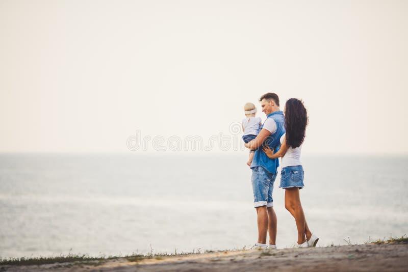 Rodzinny wakacje w naturze Trzy, mama, tata, córka jeden rok pozycja z plecy na falezie przegapia morze mężczyzna mienia hild w r obrazy royalty free