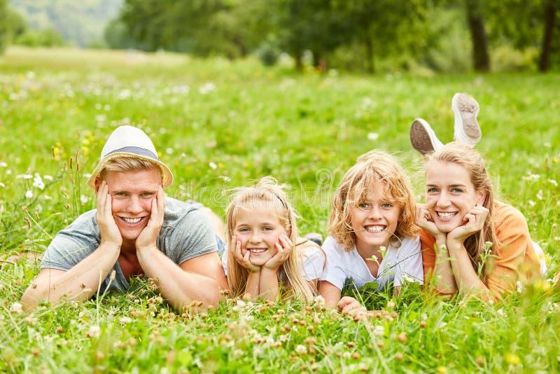 Rodziny i dzieci kłamstwo na łące zdjęcie royalty free