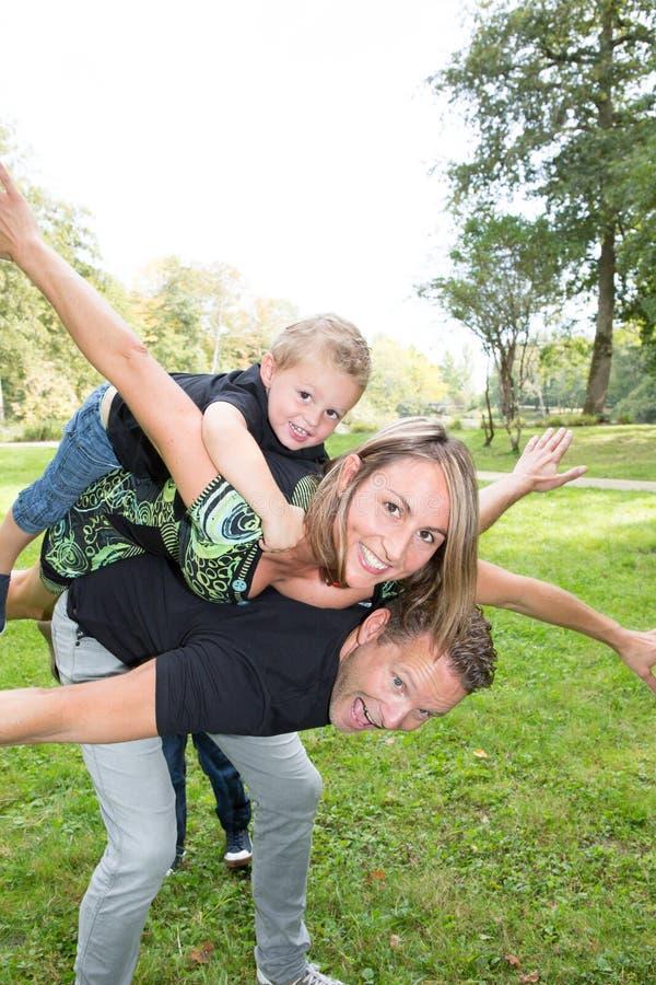 Rodziny piggyback z pięknymi macierzystymi przystojnymi blondynami i chłopiec dzieckiem ojcuje fotografia stock