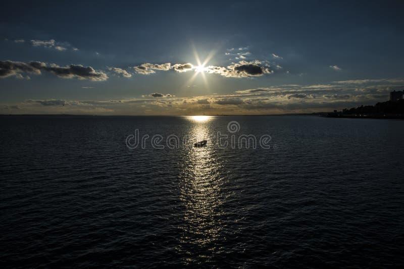 Roeiend boot in de lichtstraal van een verminderende zon wordt gehaald die Southend op Overzees, Essex royalty-vrije stock afbeelding