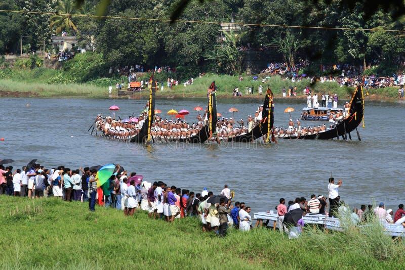 Roeiers die traditionele de kledingsrij dragen van Kerala hun slangboot in het Aranmula-bootras stock foto's