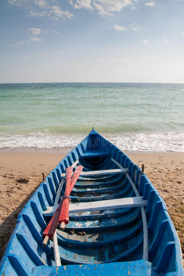Roeispaanboot op strand royalty-vrije stock afbeelding