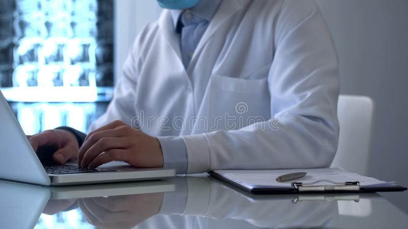Roengenologist Doktor, der an Laptop, füllende Daten in den on-line-Krankenblättern arbeitet stockbild