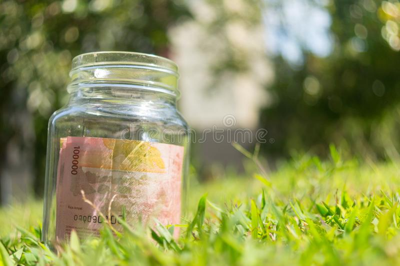 Roepiepapiergeld in kruik op Groene Aardachtergrond stock afbeeldingen