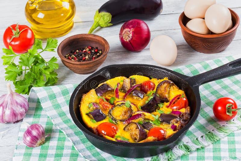 Roereieren, aubergine, ui en tomaat in pan royalty-vrije stock afbeeldingen