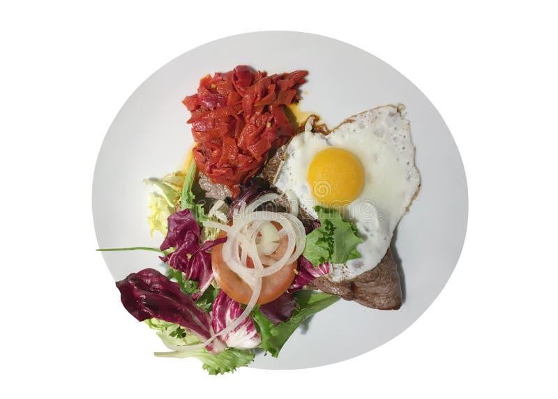 Roereieren, lapje vlees en salade op een plaat op witte achtergrond wordt geïsoleerd die stock foto