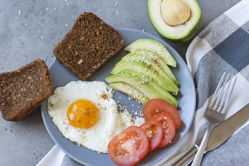 Roereieren met avocado en tomaat, geheel korrelbrood, vork, mes, handdoek stock foto