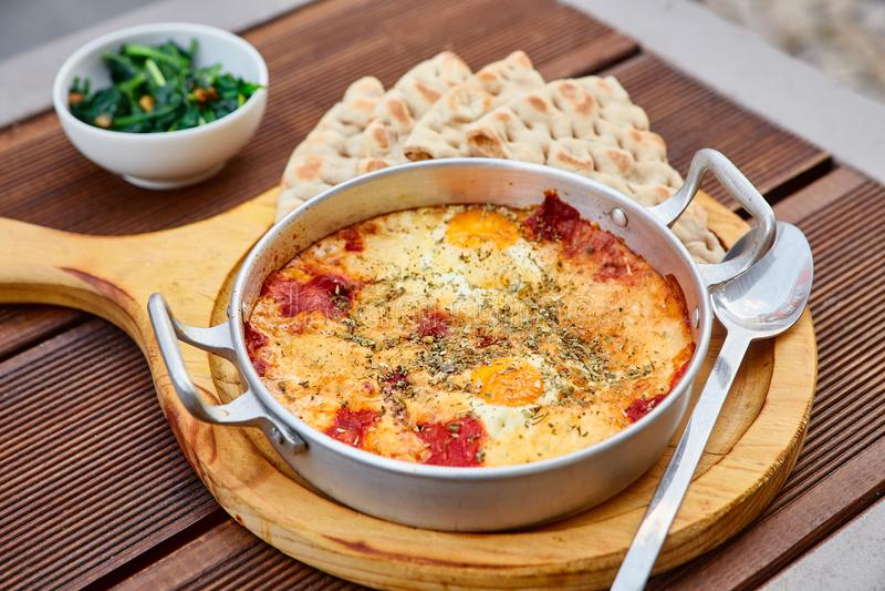 Roereieren met tomaten, kaas en kruiden in een aluminiumpan met handvatten met eigengemaakte dunne lavash en sappige greens stock foto's
