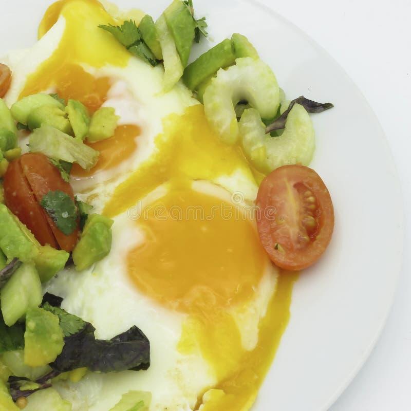 Roereieren op een witte plaat, met salade van gesneden avocado, kersentomaten, groene selderie, vers koriander en basilicum royalty-vrije stock foto