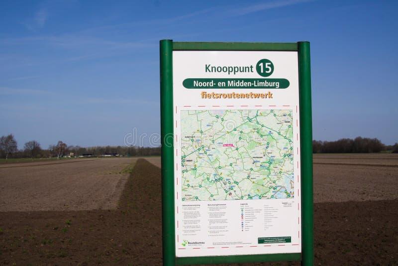 ROERMOND, holandie - MARZEC 30 2019: Znak z mapą i informacja dla rowerzystów przy złączem Knooppunt holenderski kolarstwo ślad fotografia stock