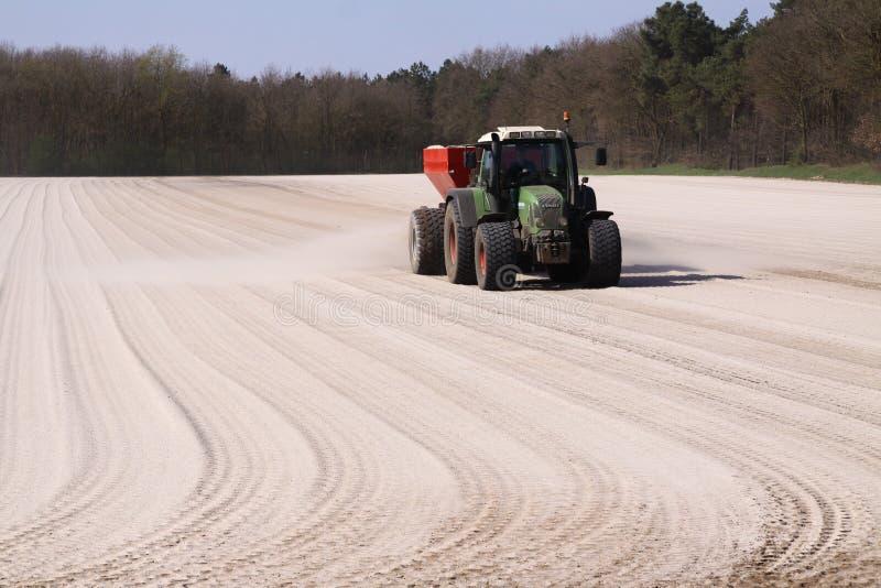 ROERMOND, PAÍSES BAJOS - 30 DE MARZO 2019: Uso de fertilizante de la tiza por el tractor con el esparcidor para preparar el campo foto de archivo libre de regalías