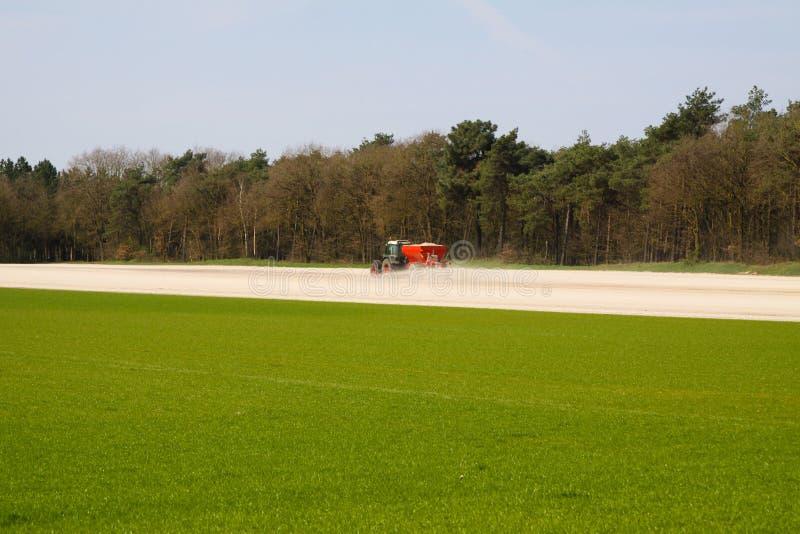 ROERMOND, PAÍSES BAJOS - 30 DE MARZO 2019: Uso de fertilizante de la tiza por el tractor con el esparcidor para preparar el campo imagen de archivo