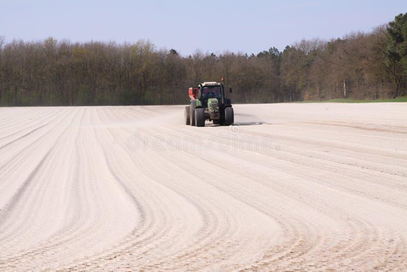ROERMOND SOM ÄR NEDERLÄNDSK - MARS 30 2019: Kritagödningsmedelapplikation vid traktoren med spreaderen som förbereder fältet royaltyfri fotografi