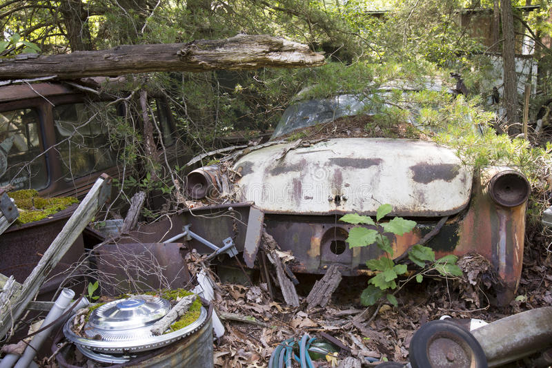 Roestende klassieke auto in autokerkhof stock foto's