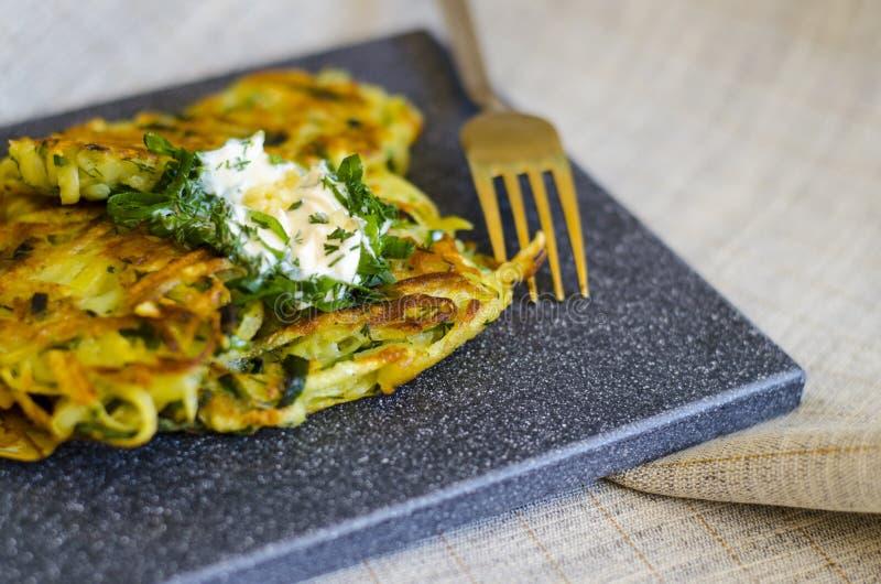 Roesti Πατάτες που ξύνονται με τα πράσινα που τηγανίζονται στο βούτυρο Χορτοφάγος πίνακας στοκ φωτογραφίες