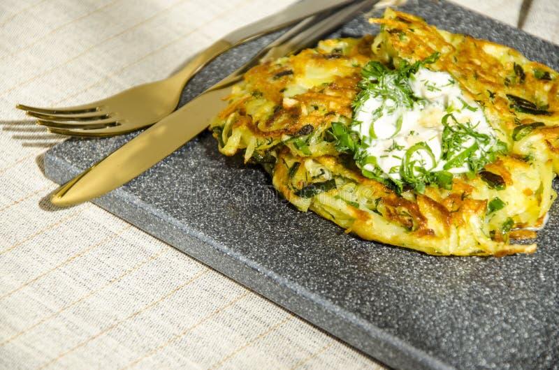 Roesti Les pommes de terre ont râpé avec des verts frites en beurre Table v?g?tarienne photographie stock