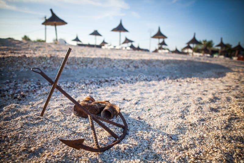 Roestig anker op een zandig strand royalty-vrije stock foto