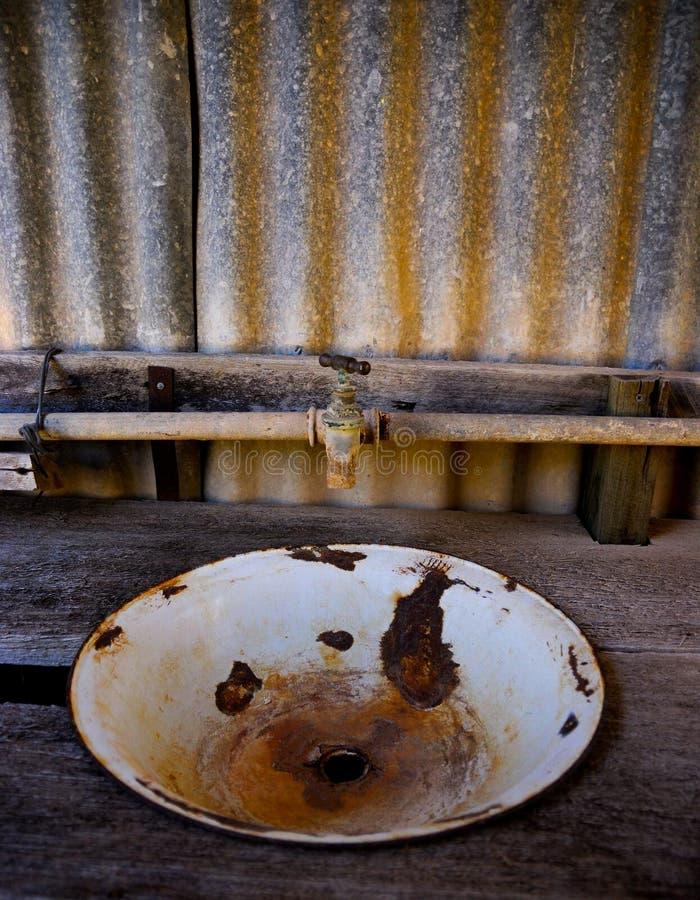 Roestig en afgebroken wasbassin op houten bank stock foto