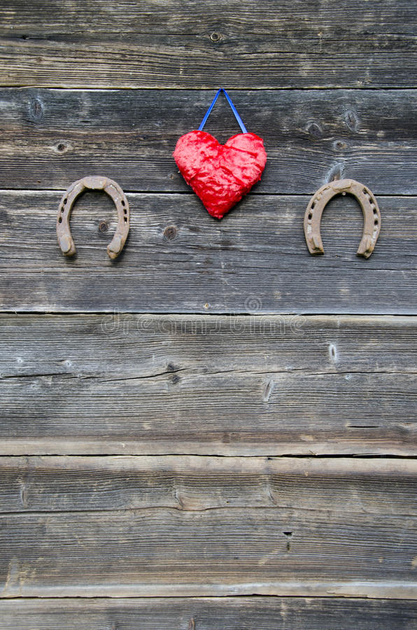Roestig hoef twee en hartsymbool op houten muur stock foto