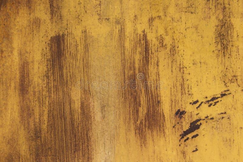 Roestig ijzer als achtergrond met resten van gekleurde verf Oranje Achtergrond stock foto