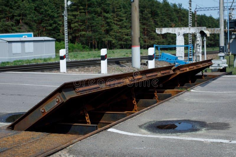Roestige barrière bij een spoorwegovergang tegen de achtergrond van de bosvulklei op de bestrating Het concept hindernissen, eind stock foto