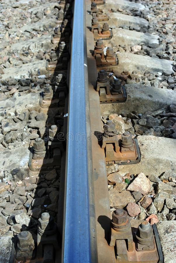 Roestige bouten langs metaaloppervlakte van spoorwegsporen, verpletterde stenen stock foto