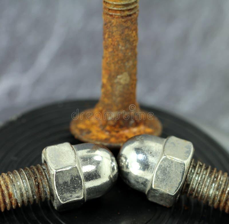 Roestige die schroeven met hoedennoot van chroom wordt gemaakt stock foto