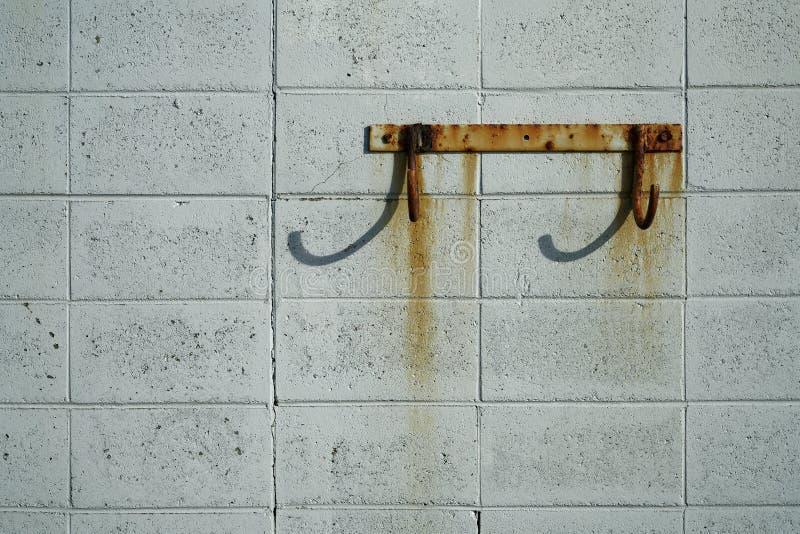 Roestige haken op een muur van het windblok royalty-vrije stock fotografie