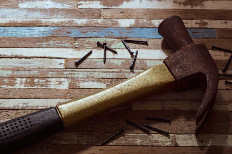 Roestige hamer met spijkers op een grunge houten achtergrond stock foto's