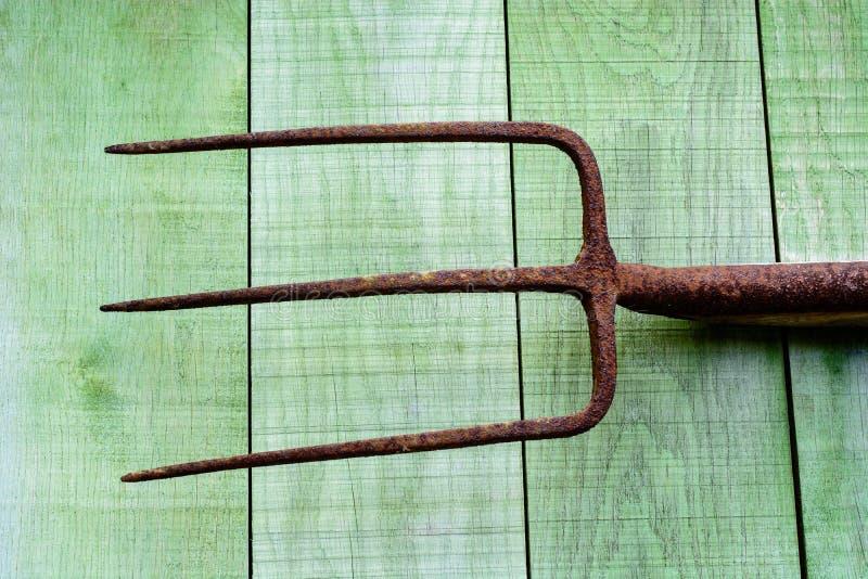 Roestige hooivork op houten planken stock foto's