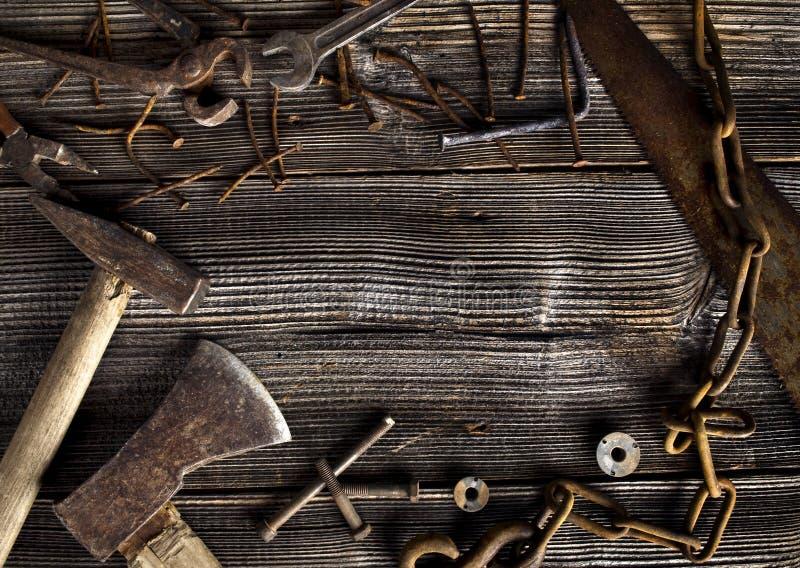 Roestige hulpmiddelen op oude donkere plank stock foto's