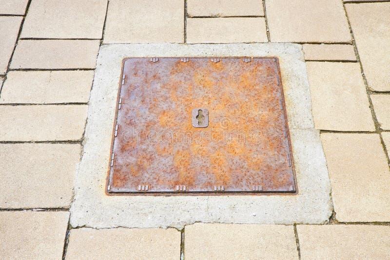 Roestige ijzer gegoten mangaten in het moderne steen bedekken royalty-vrije stock foto's