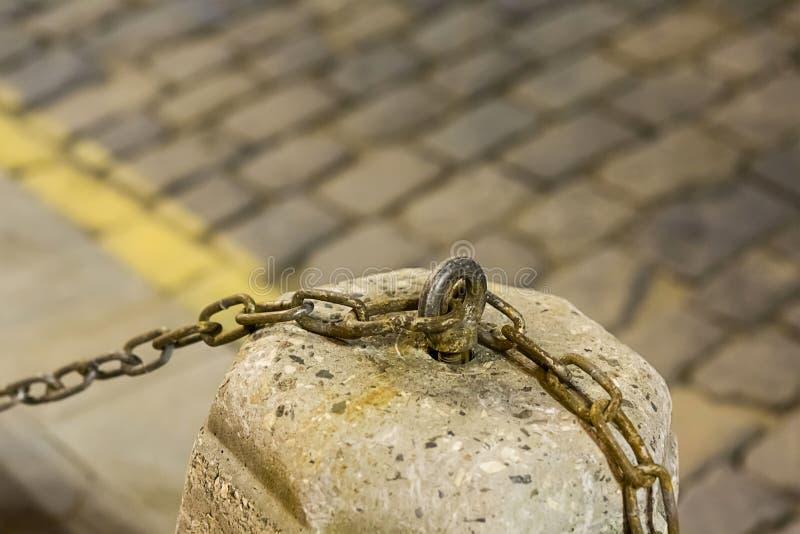 Roestige ijzerketting vastgehaakt aan het cementvoetstuk op de vage achtergrond van de stedelijk gebiedsstraatstenen royalty-vrije stock afbeelding