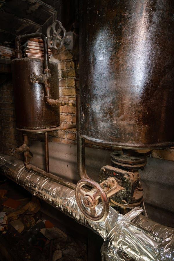 Roestige ketelruimpijpen Oude metaalboiler die het verwarmen produceren en het leveren aan huis door pijpleiding Het warme water  stock fotografie