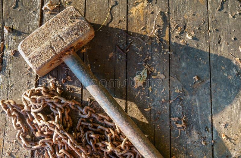 Roestige ketting en oude hamer op grijze stenen Een gescheurde ketting is een symbool van bevrijde arbeid stock afbeeldingen