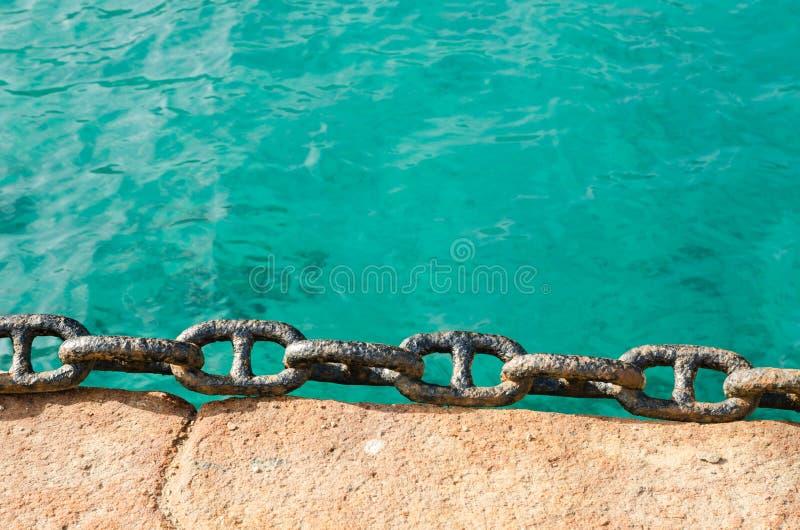 Roestige ketting op een dok, met de Middellandse Zee stock foto's