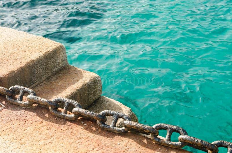 Roestige ketting op een dok, met de Middellandse Zee als achtergrond stock foto