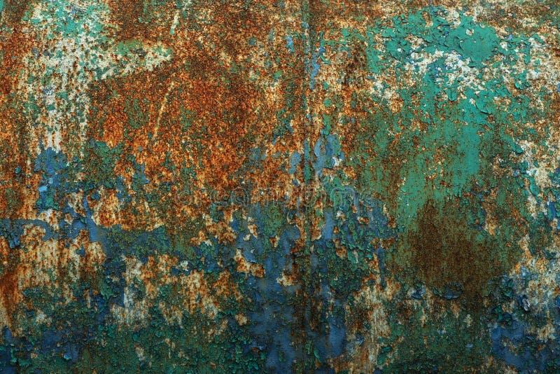 Roestige metaalmuur, oud die ijzerblad, met roest met multi-colored verf wordt behandeld Spoor van rest van oude verf in grote di stock foto's