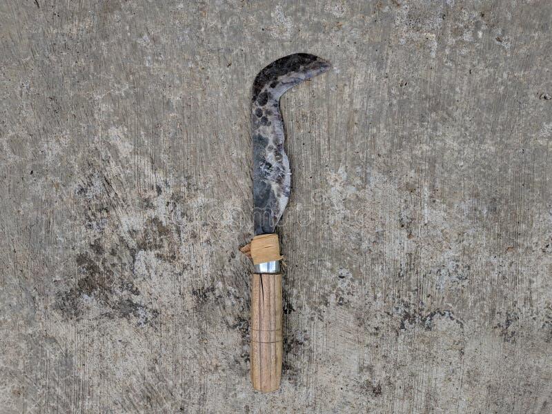 Roestige metaalsikkel op concrete textuur stock afbeelding
