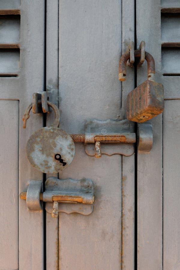 Roestige oude hangsloten en sluitenbouten op metaaldeuren stock afbeelding