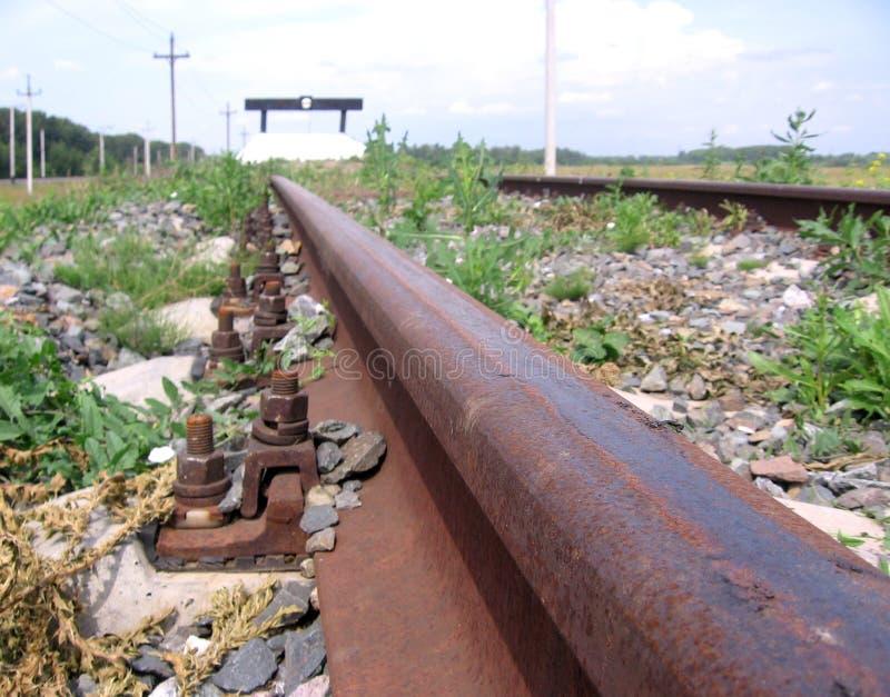 Roestige sporen van een ongebruikte overwoekerd weg van het impassespoor stock foto's