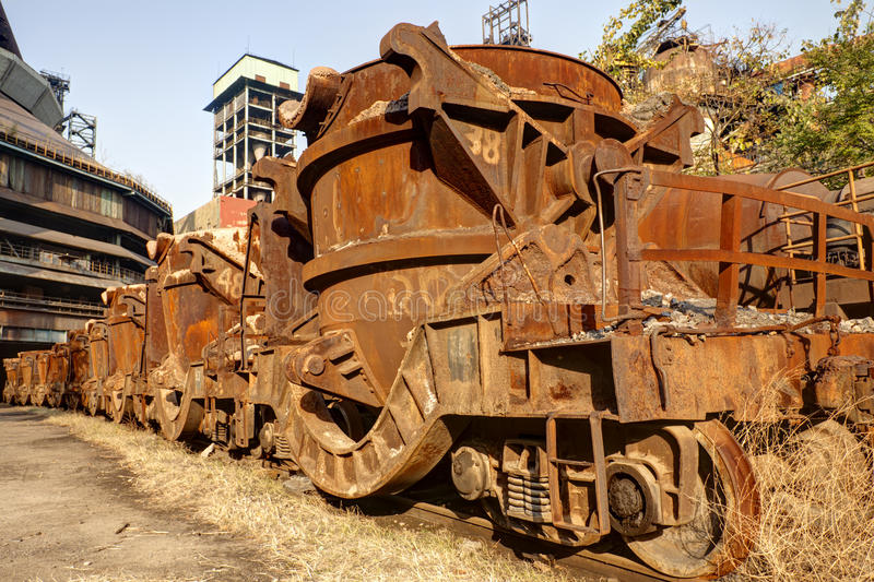 Roestige trein bij verlaten staalfabriek stock fotografie