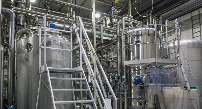 Roestvrij staal het brouwen materiaal: grote tanks en pijpen in moderne bierfabriek Brouwerijproductie, industriële achtergrond stock afbeeldingen