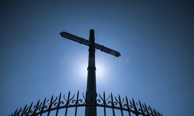 Roestvrij staalkruis en omheining op blauwe hemel en zon lichte achtergrond Kruisbeeld van Jesus Christ God-licht en vergiffenisc royalty-vrije stock afbeeldingen