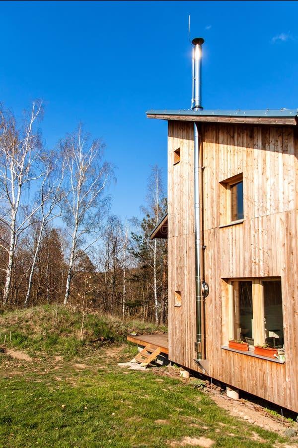 Roestvrij staalschoorsteen bij de ecologische houten bouw De bouw van een familiehuis Het verwarmen van het huis met hout stock foto