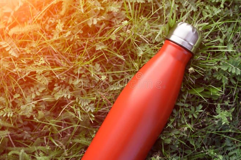 Roestvrije flessenthermosflessen, rode kleur Op de groene grasachtergrond royalty-vrije stock fotografie